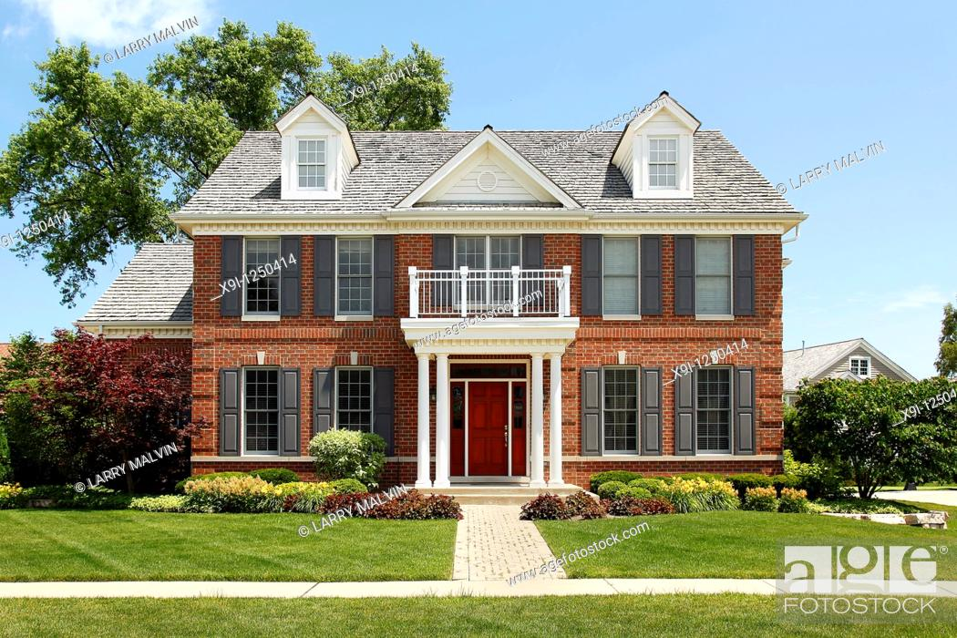 Stock Photo: Brick home with columned entry and front balcony.