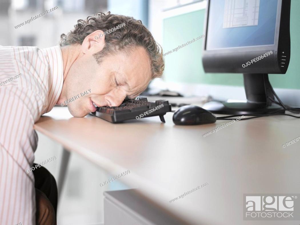 Stock Photo: Businessman sleeping on computer keyboard.