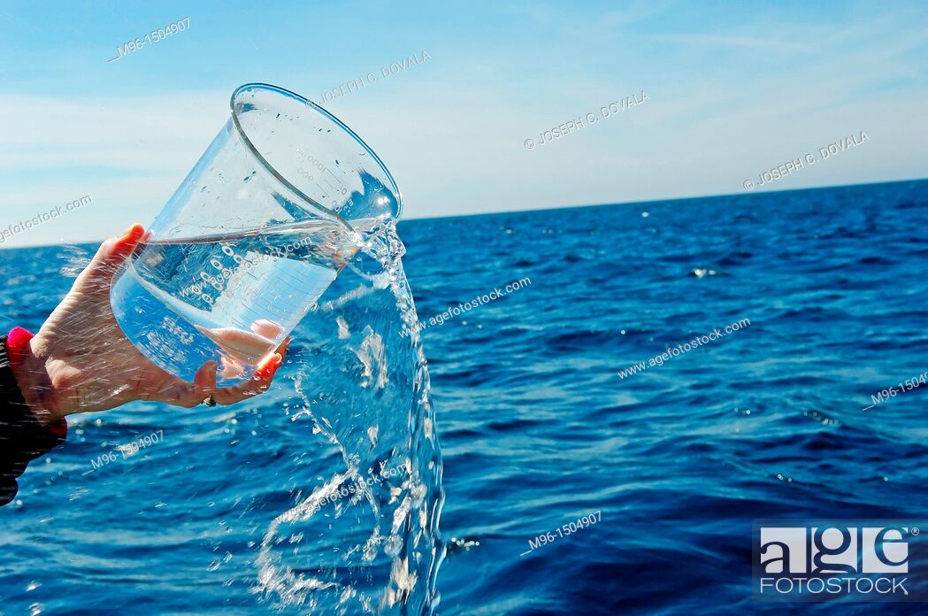 Stock Photo: Pouring sea water from beaker on ocean.