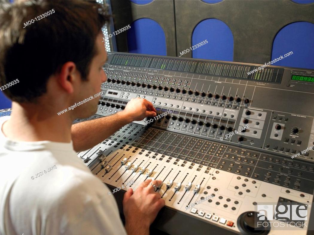 Stock Photo: Sound technician in recording studio back view.