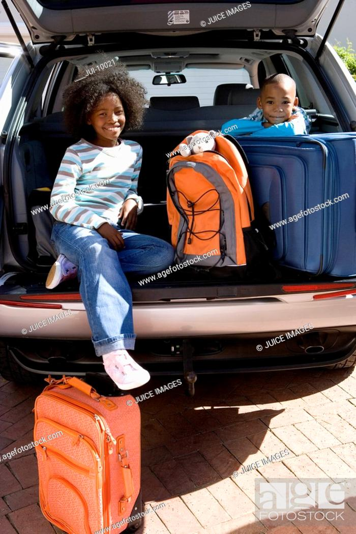 Stock Photo: Brother and sister 6-10 in back of car with luggage, smiling, portrait.