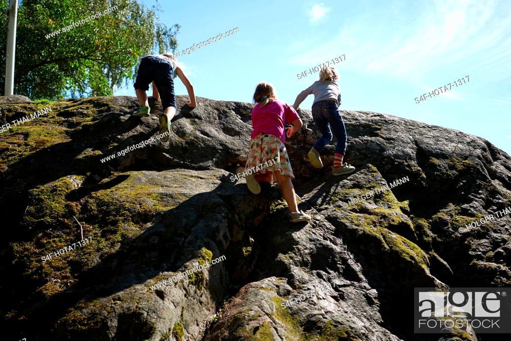 Stock Photo: Schweden, Insel Grinda, Kinder klettern auf einen Felsen.