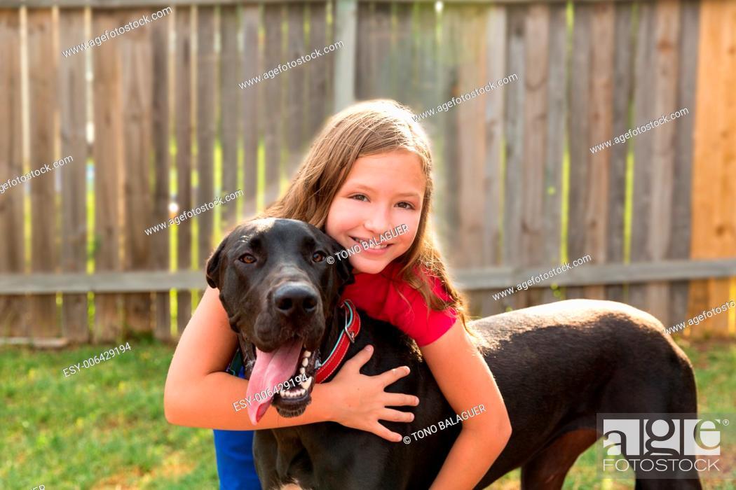 Stock Photo: great dane and kid girl hug playing together at backyard outdoor.