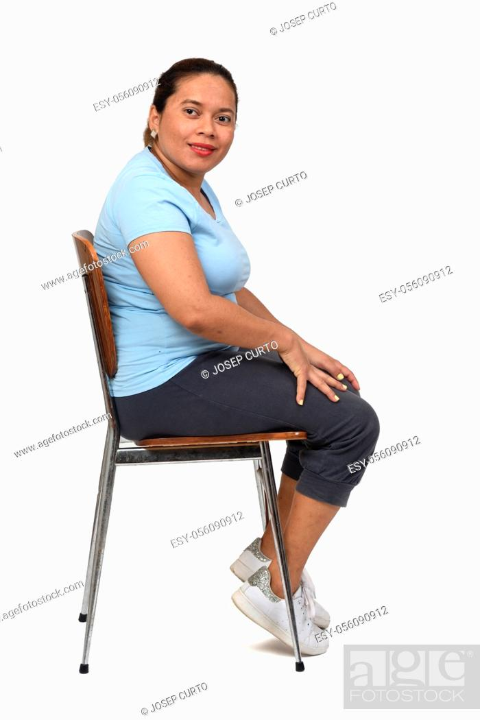 Photo de stock: side view of a woman sitting on a chair looking at camera on white background.