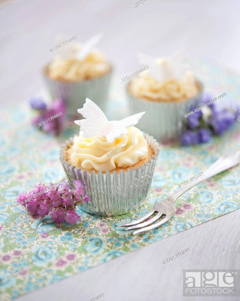 Stock Photo: White chocolate cupcakes decorated with buttercream.