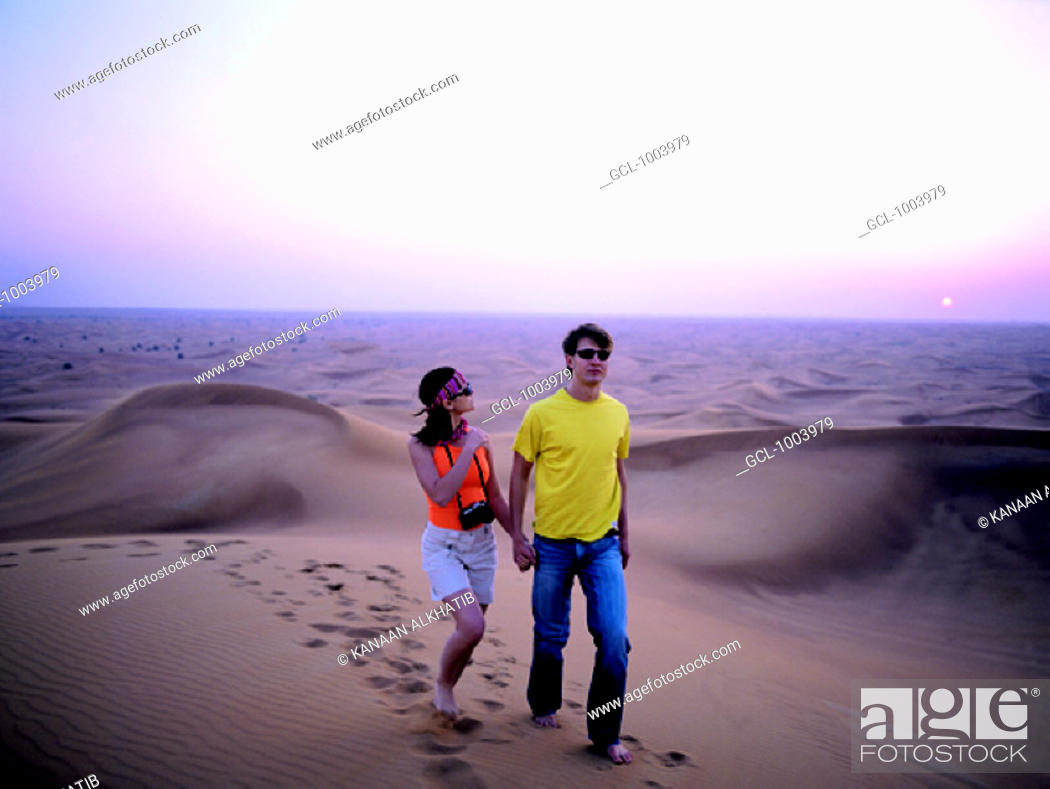 Stock Photo: Western couple walking in the desert near Hatta, United Arab Emirates.