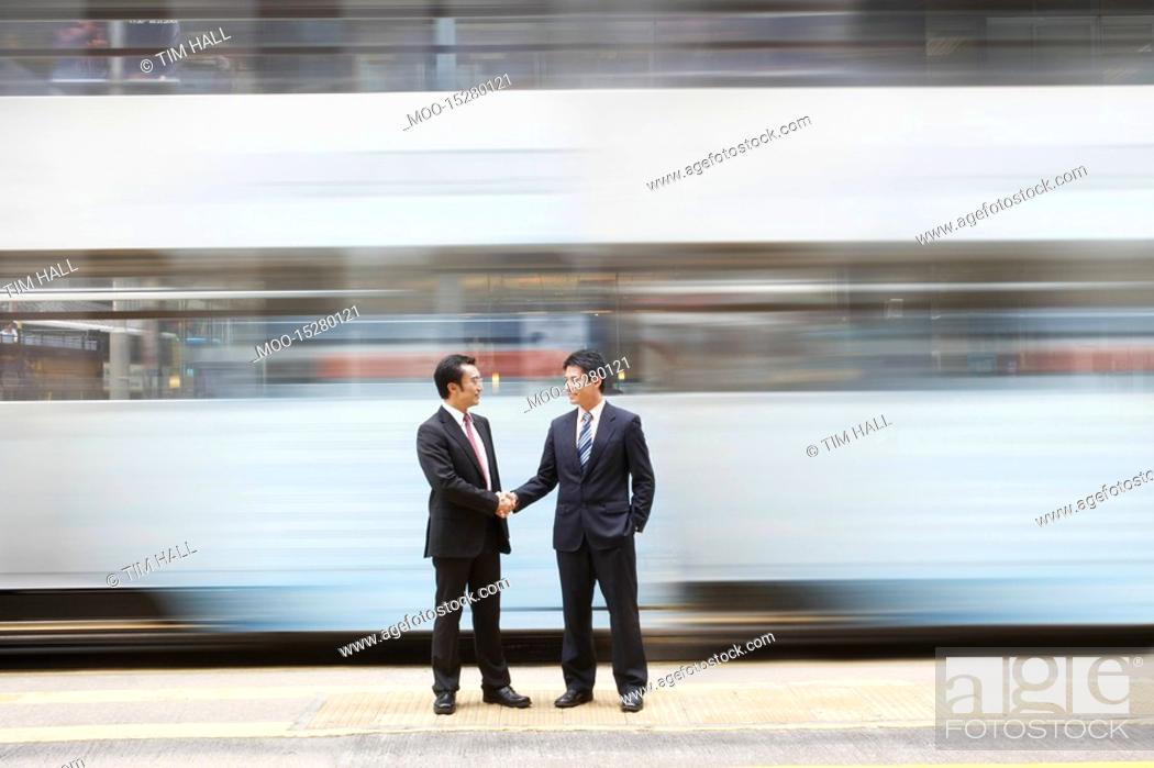Stock Photo: China Hong Kong two business man shaking hands standing on street crossing long exposure.