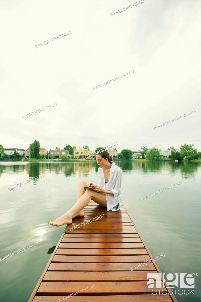 Stock Photo: Woman sitting on lake dock using digital tablet.