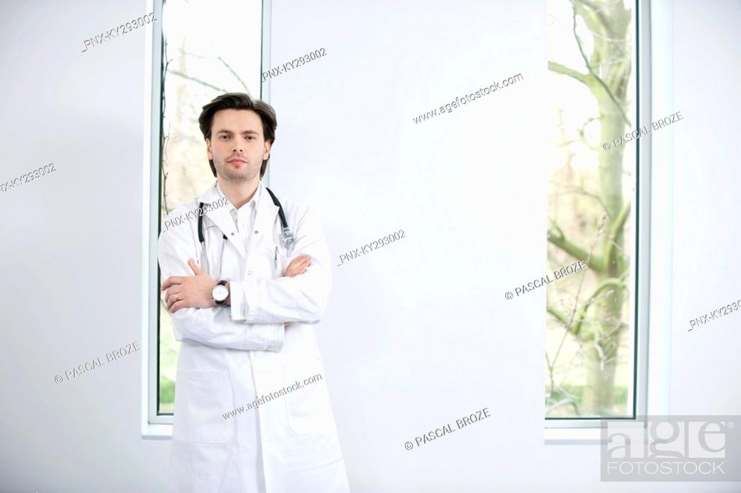 Stock Photo: Portrait of a doctor standing with his arms crossed.