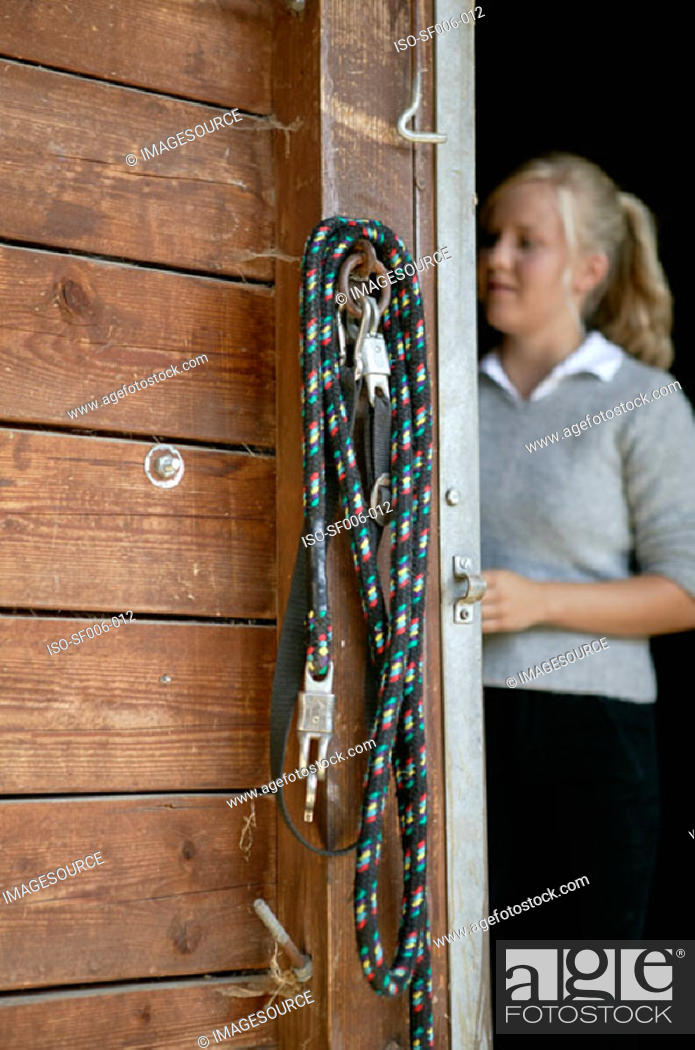 Stock Photo: Young woman at stable door.