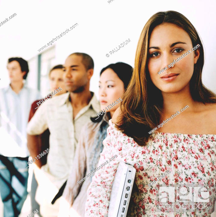 Stock Photo: Young woman smiling looking at camera with a group of young people behind her.