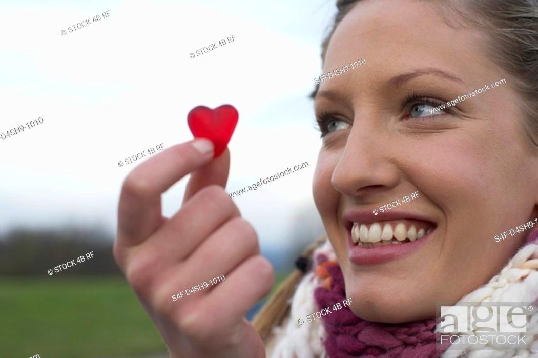 Stock Photo: Young woman with scarf is holding a gummi-bear heart in her hand , close-up.