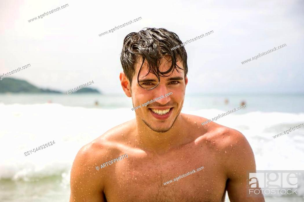Stock Photo: Handsome young man standing on a beach in Phuket Island, Thailand, shirtless wearing boxer shorts, showing muscular fit body.