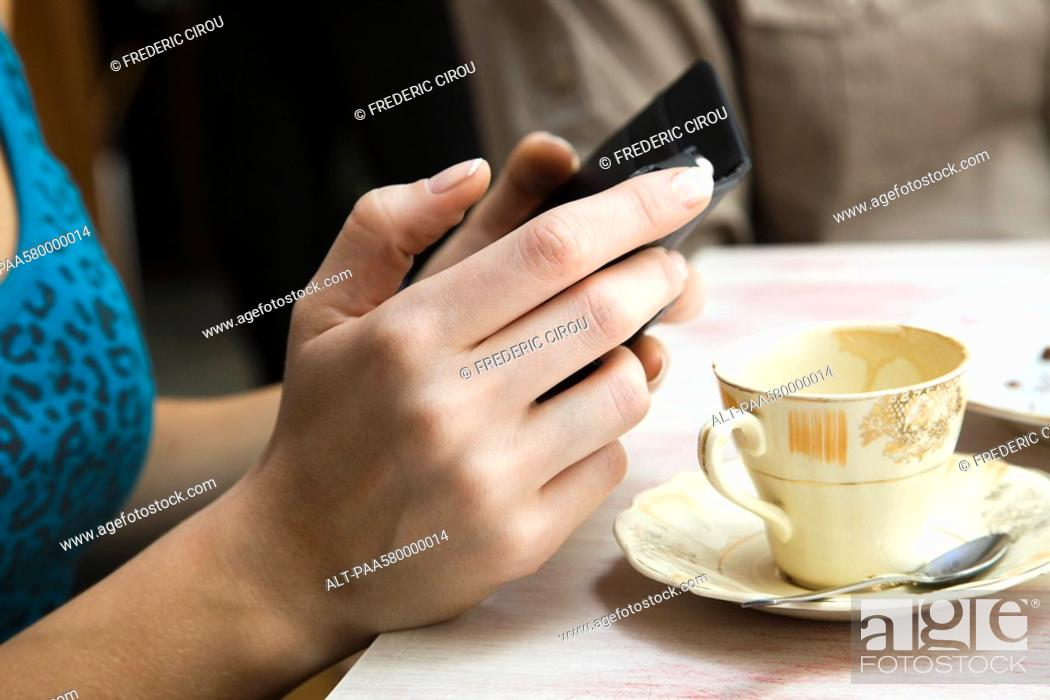 Stock Photo: Woman holding cell phone, close-up.