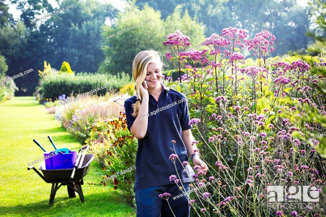 Imagen: Female gardener at Waterperry Gardens in Oxfordshire, using a mobile phone.