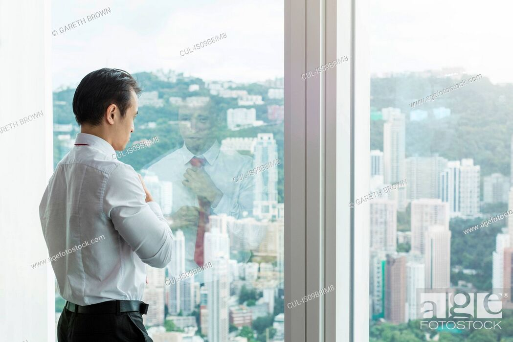 Stock Photo: Businesswoman looking out of window.