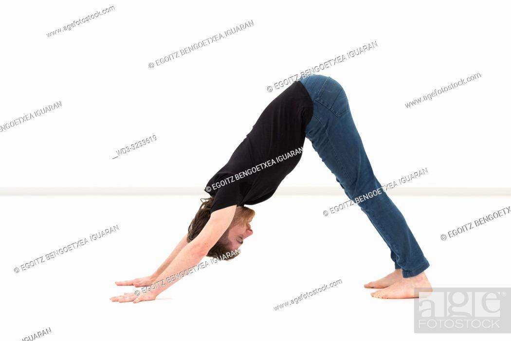 Imagen: Casual dressed young adult man stretching on white background.