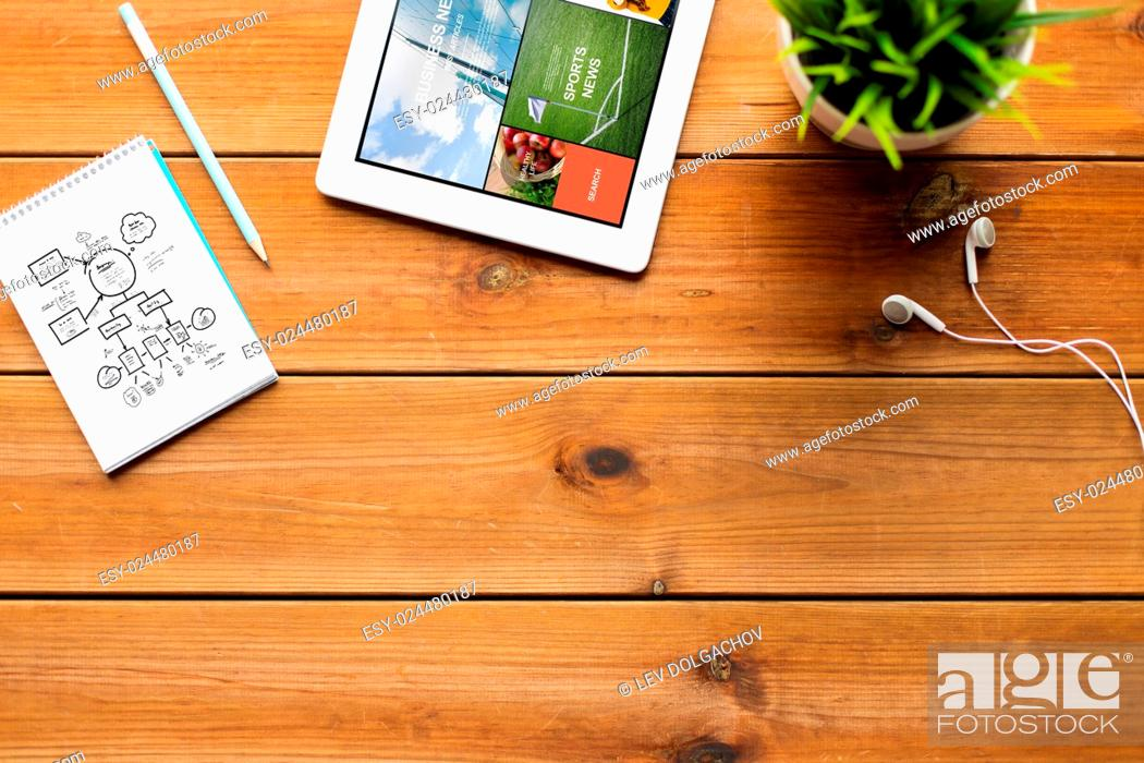 Stock Photo: mass media, business and technology concept - close up of tablet pc computer with internet news application on screen, notebook with scheme.