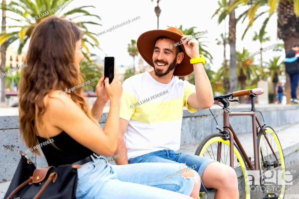 Photo de stock: Spain, Barcelona, happy couple sitting on bench taking a smartphone picture.