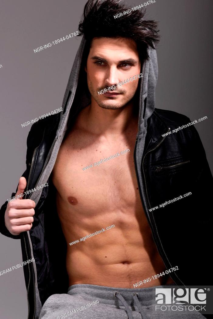 Stock Photo: Portrait of athletic man wearing hoodie jacket. Studio shot.
