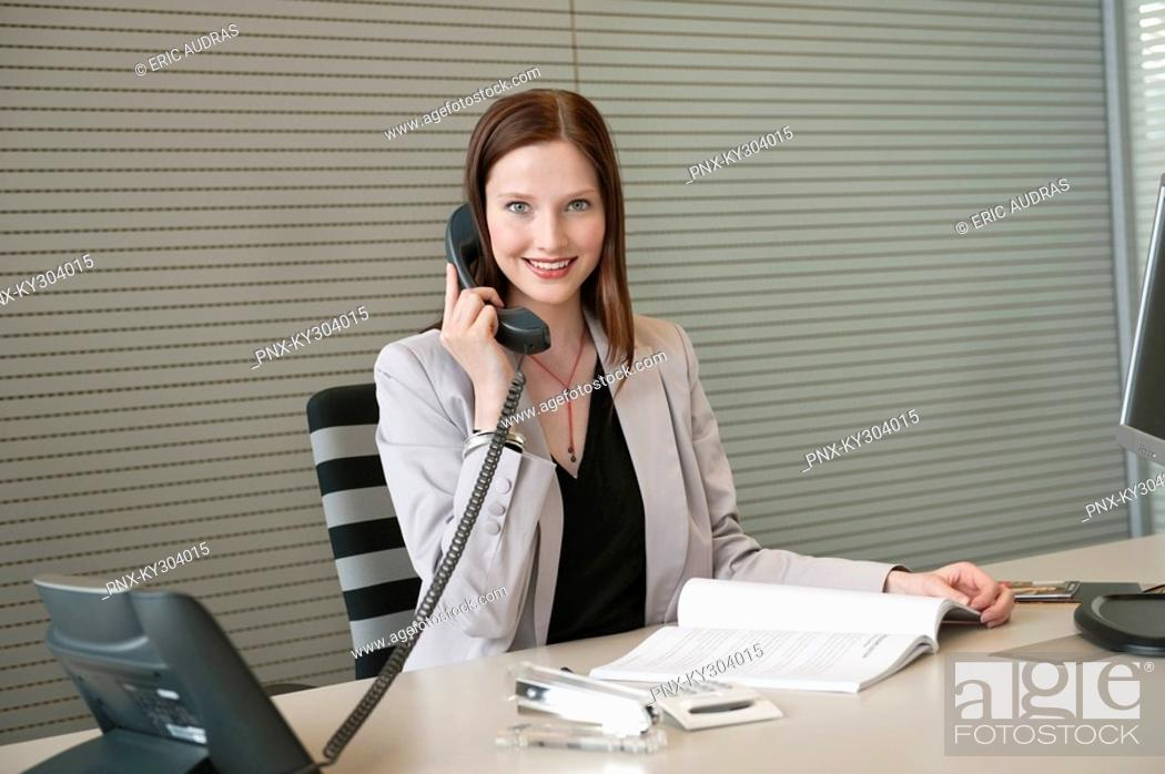 Stock Photo: Businesswoman talking on a telephone in an office.