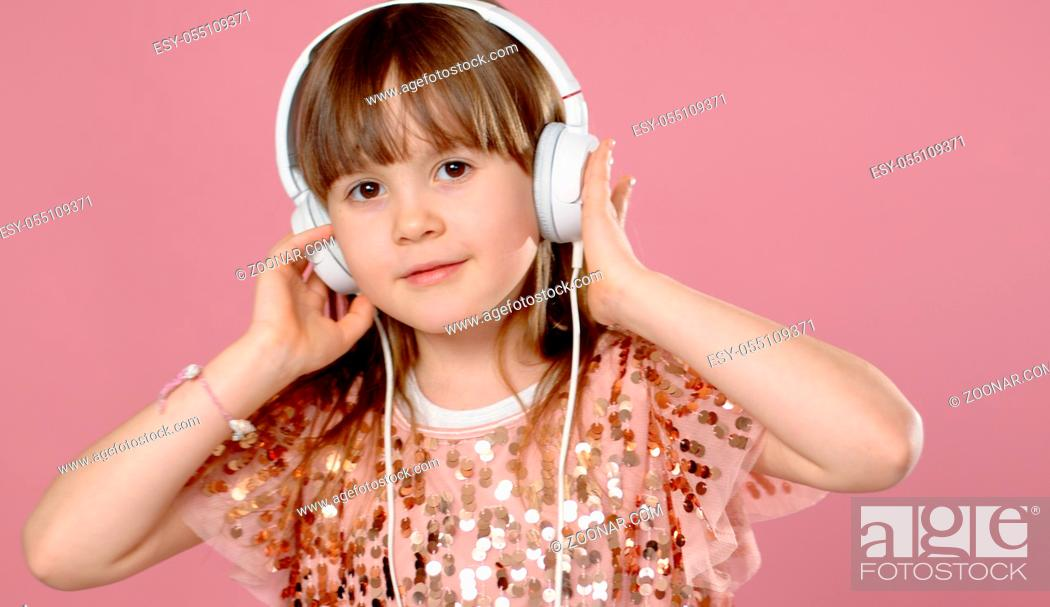 Stock Photo: Cute little girl posing and dancing with headphones while listen to the music. Standing isolated on pink background with copyspace.