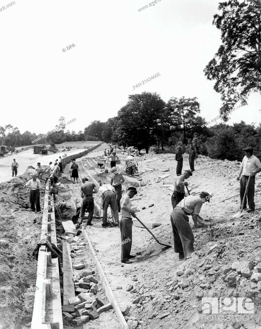 Stock Photo: Workers reconstruct the Avus road in Berlin, Germany, in the spring of 1951. The Avus was the site of Germany's first car race after the end of the 2nd World.