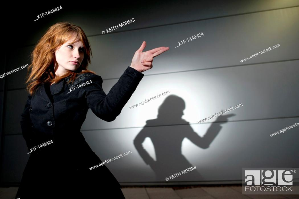 Stock Photo: A late teen early 20s single woman girl with red hair pointing her fingers like a gun, casting shadow, UK.