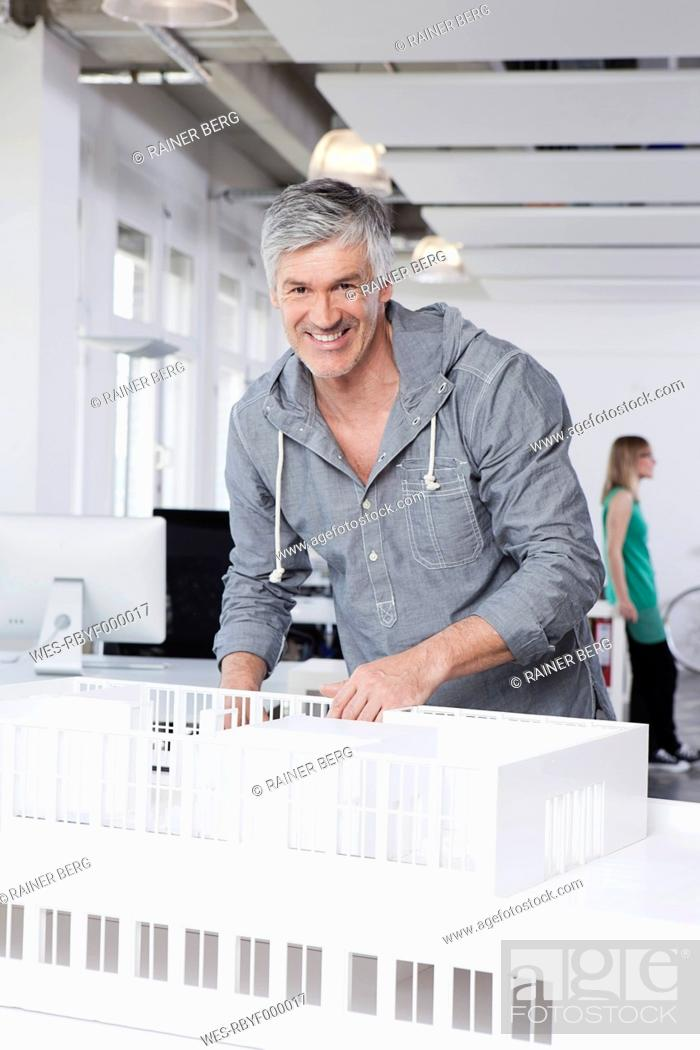 Stock Photo: Germany, Bavaria, Munich, Man standing with architectural model in office.