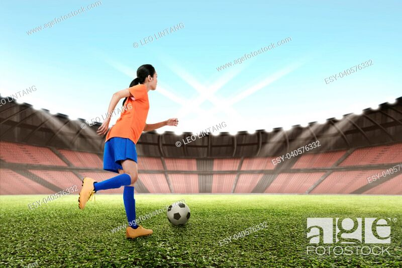 Stock Photo: Image of asian female footballer kicking the ball on the field.