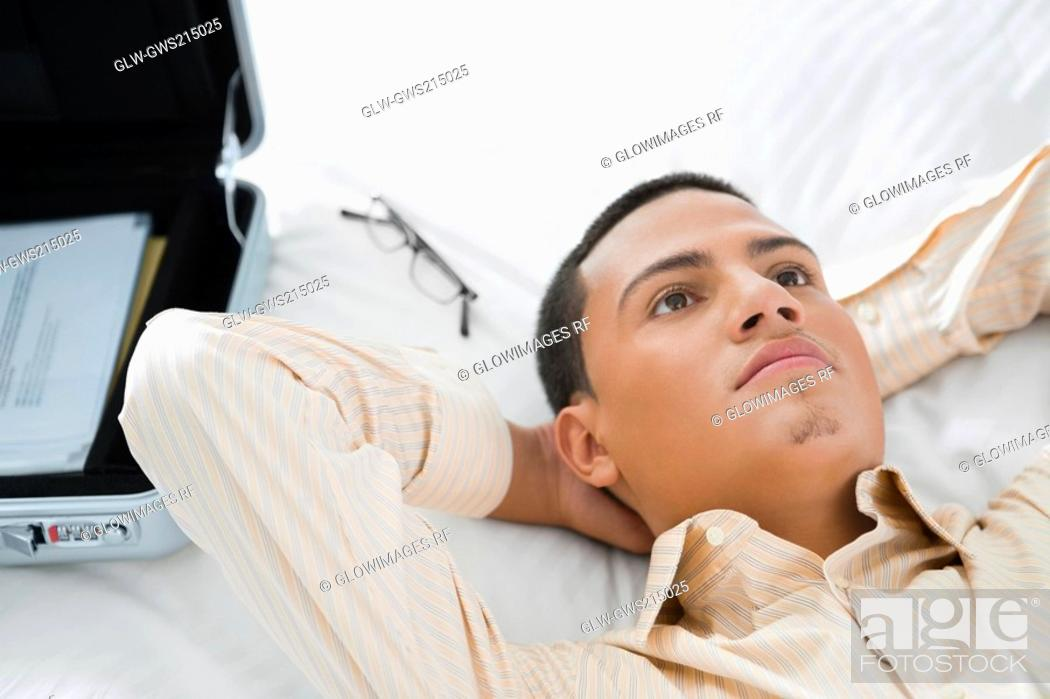 Stock Photo: Businessman lying on the bed and thinking.