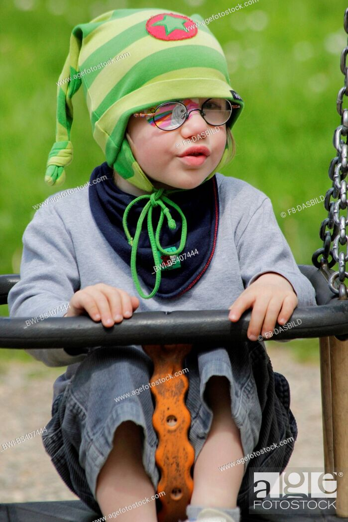 Stock Photo: little girl with eye patch sitting amused in a swing, Germany.