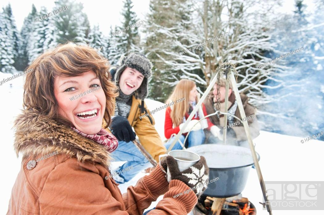 Stock Photo: Austria, Salzburg Country, Flachau, Young men and women sitting near fireplace and making tea in snow.