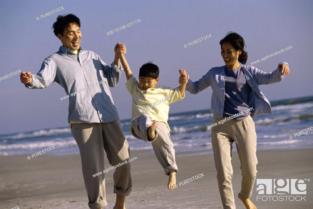 Stock Photo: Parents carrying their son on the beach.