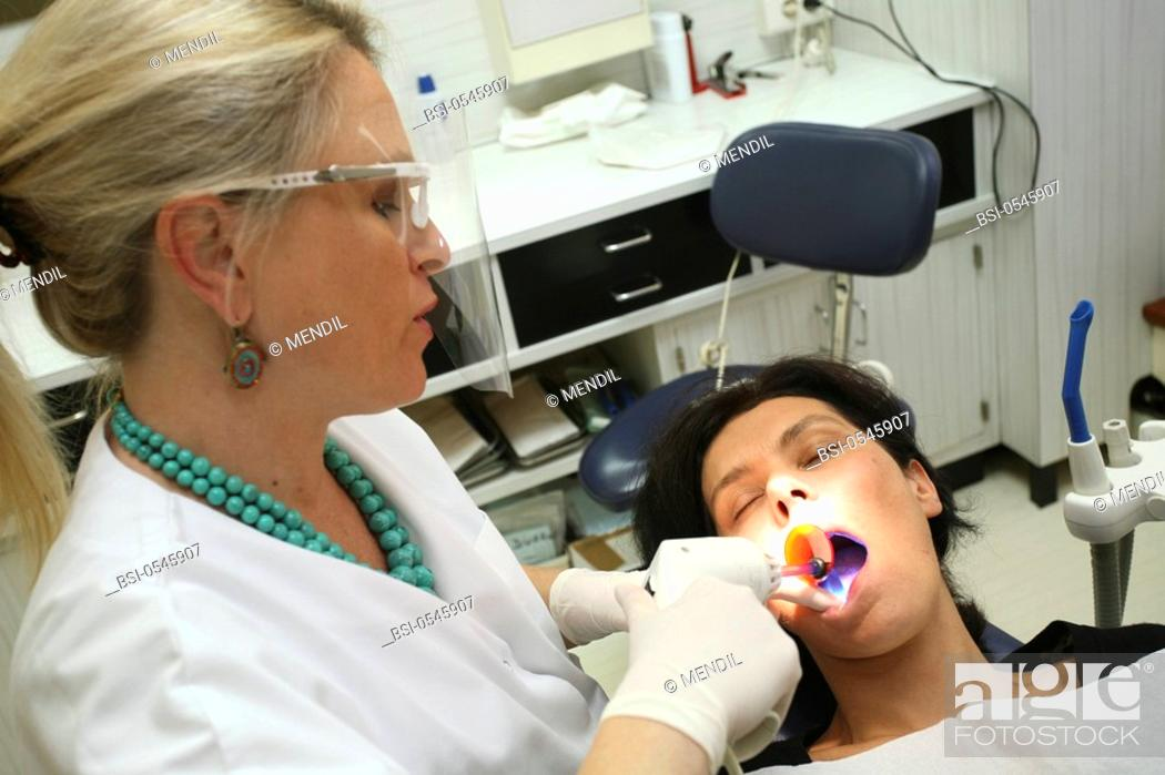 Imagen: WOMAN RECEIVING DENTAL CARE Photo essay from dental office. Use of a curing light to harden the composite.