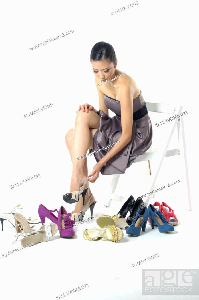 Stock Photo: Woman adjusting straps of her sandal.