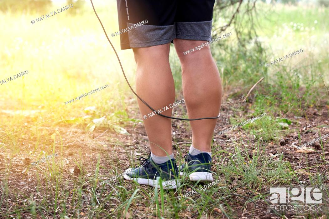 Stock Photo: adult man in blue clothes holding a jump rope for playing sports, standing sideways against the setting sun, summer day in the middle of a coniferous forest.