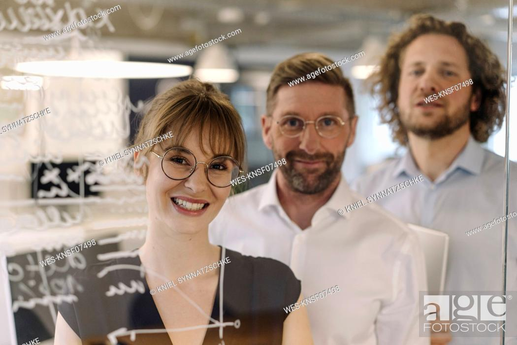 Stock Photo: Portrait of confident business team behind a glass pane in office.