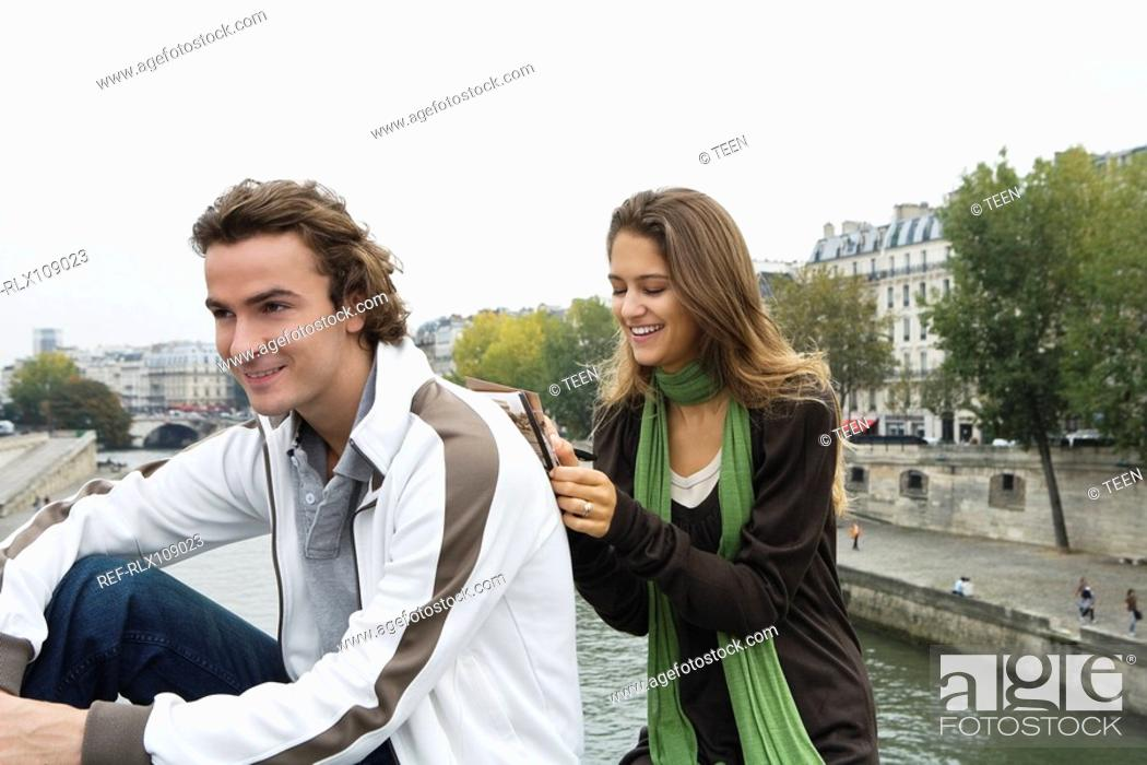 Stock Photo: Young couple sitting on bridge, woman leaning on mans back writing postcard.
