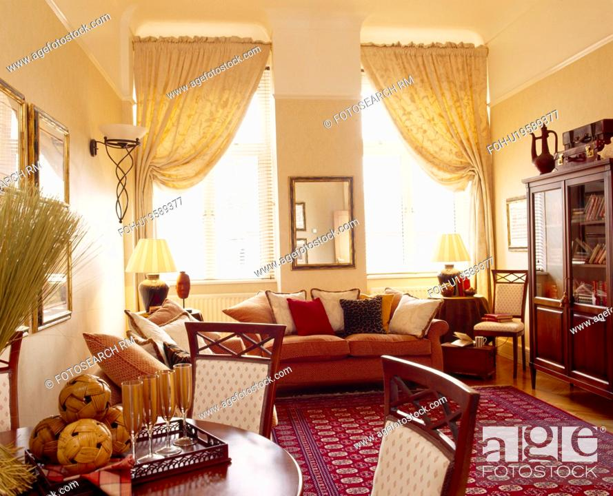 Cream Curtains And Patterned Red Oriental Carpet In Apartment Living