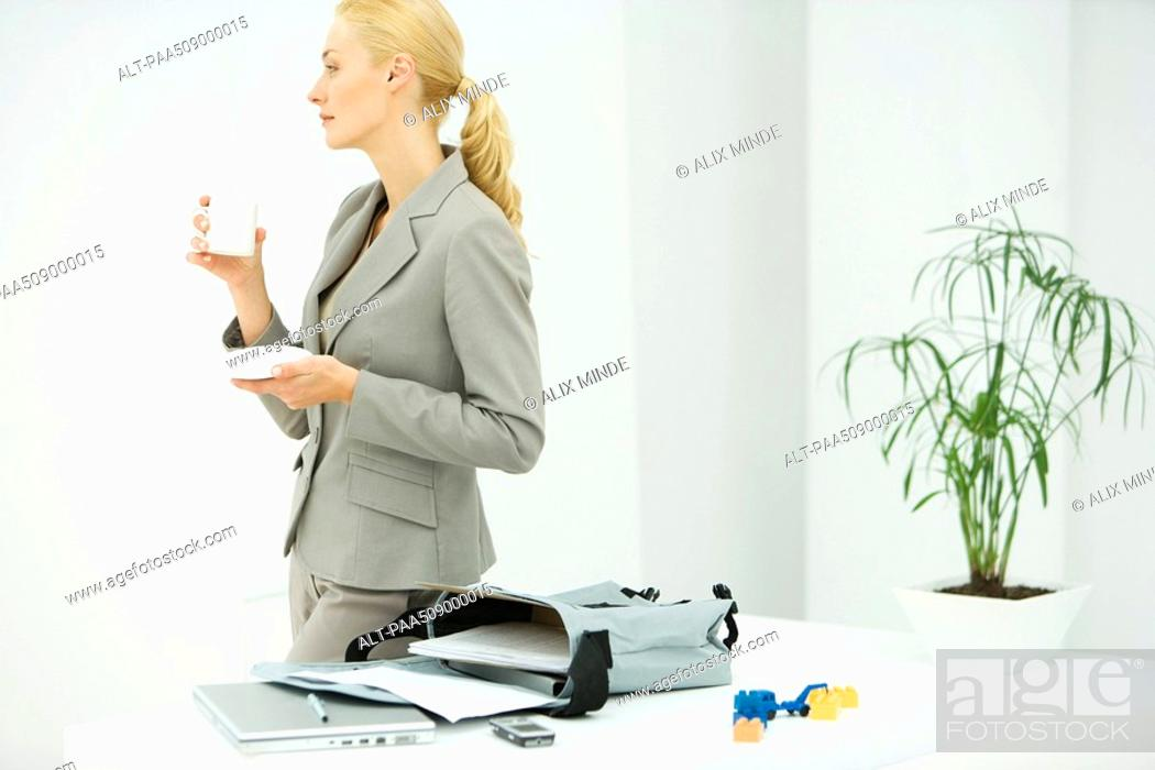 Stock Photo: Professional woman holding coffee cup, looking away, bag with laptop and documents on table.