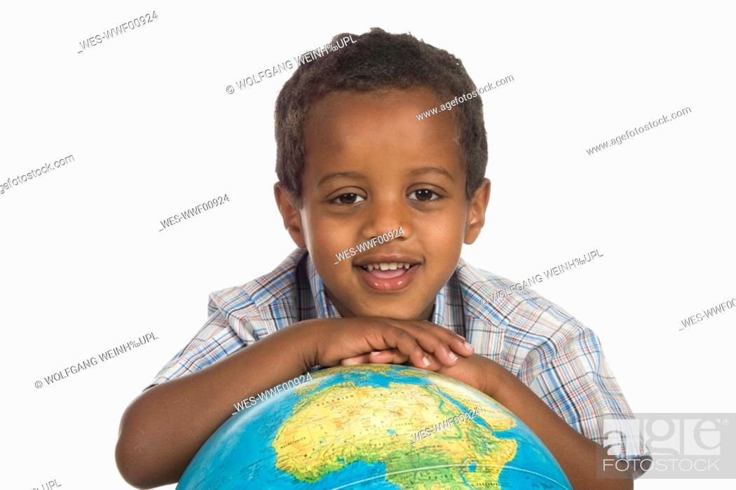 Stock Photo: African boy 3-4 with globe, portrait.