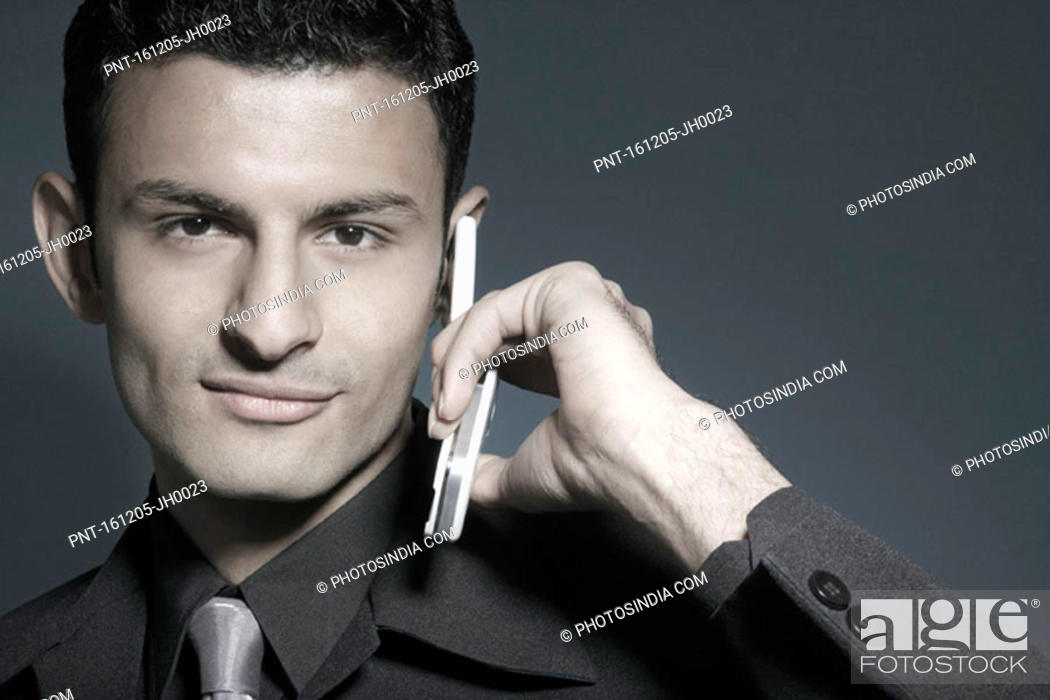 Stock Photo: Portrait of a businessman holding a mobile phone.