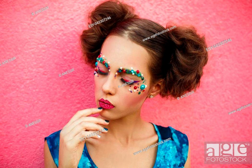 Stock Photo: Fashion closeup shot of fashion face of pretty girl with two hair buns and closed eyes on pink background.