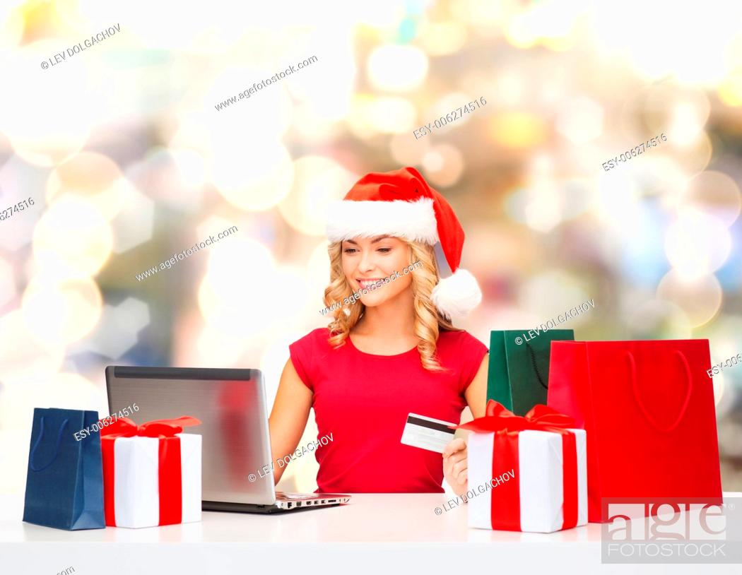 Stock Photo: christmas, holidays, technology and shopping concept - smiling woman in santa helper hat with gifts, credit card and laptop computer over lights background.