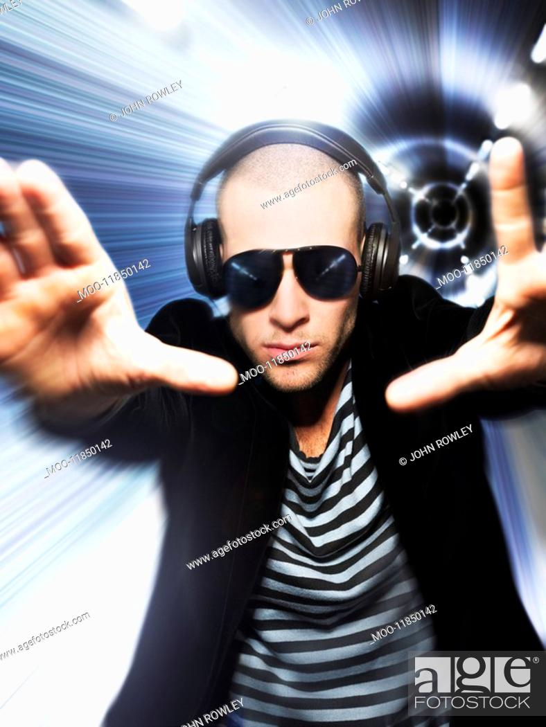 Stock Photo: Man wearing headphones in front of tunnel effect view through hands.