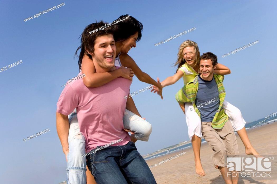 Stock Photo: Young men piggybacking women on beach.