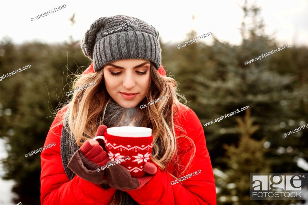 Stock Photo: Portrait of young woman with coffee in christmas tree forest.