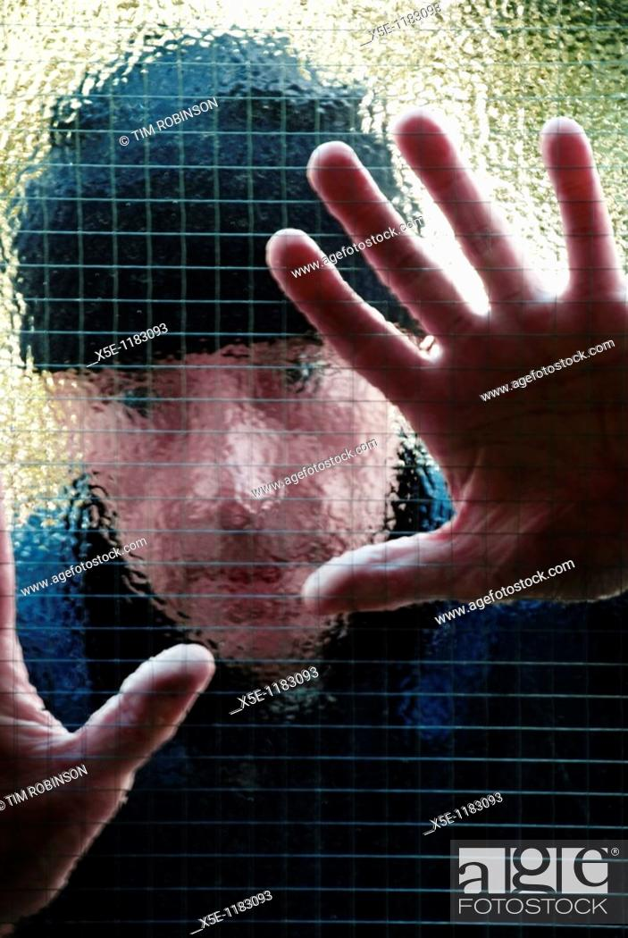 Stock Photo: Head and shoulders of suspicious man peering through window.