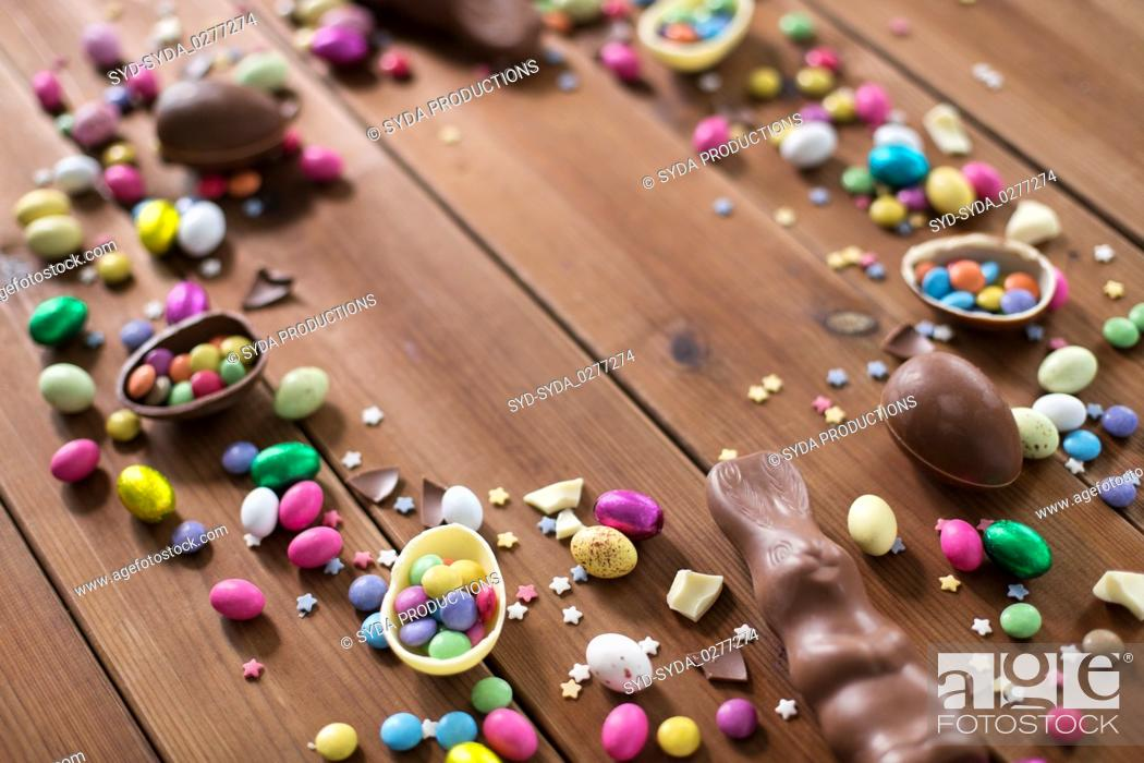 Stock Photo: chocolate eggs and candy drops on wooden table.